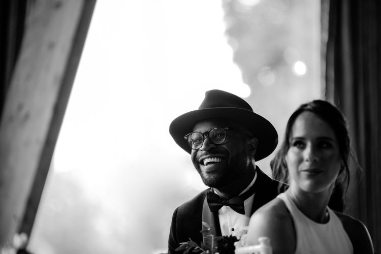 Stylish groom in Fedora hat smiling during the wedding reception speeches