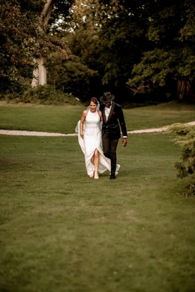 Stylish bride and groom walking arm in arm
