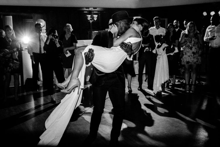 Groom sweeping his bride off her feet at The Ravenswood evening reception