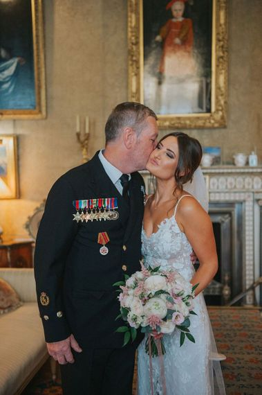 Father of the Bride Kissing Bride on Cheek wearing Military Medals