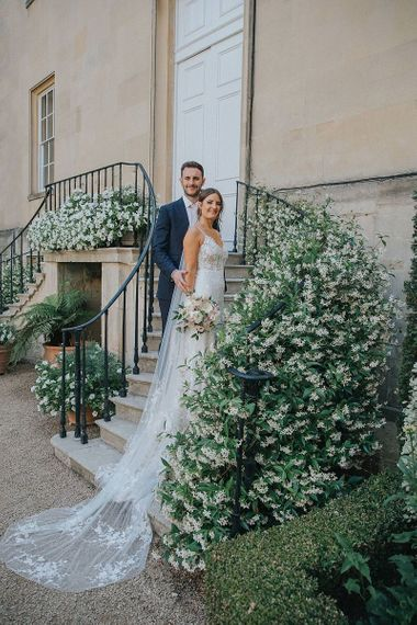 Bride and Groom on Staircase with White Floral Foliage  In Navy Suit and Lace Dress