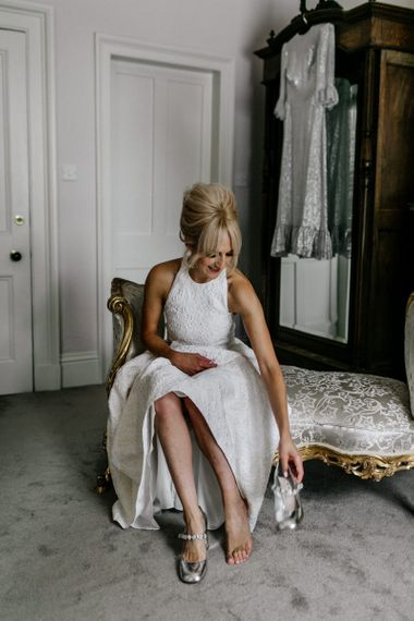 Bride in Charlie Brear Wedding Dress Putting on Miu Miu Shoes