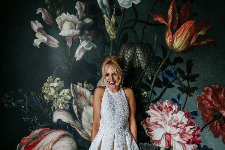 Bride in Charlie Brear Dress Against Painted Flower Wall