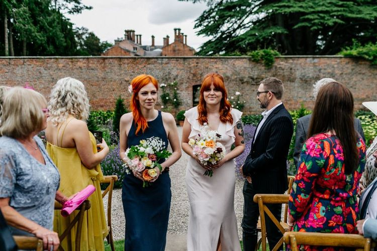 Two Bridesmaids In Navy And Pink Walk Down The Aisle