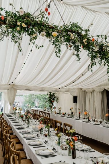 Marquee Reception with Floral Beam Hanging and Bright Flowers in Vintage Jars on Table