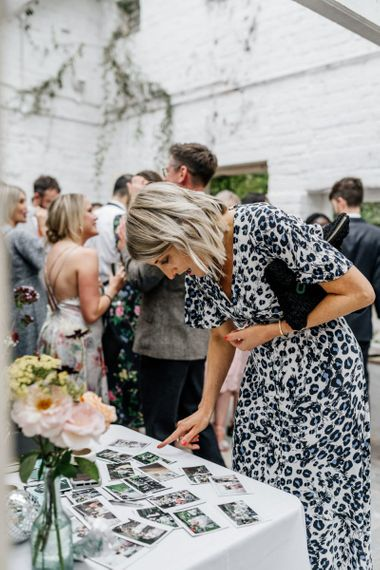 Wedding Guest Looks Through Polaroid Photos At Wedding