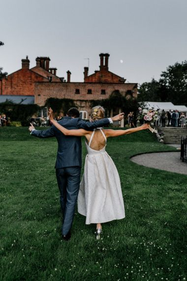 Open Back Charlie Brear Wedding Dress and Grey Suit