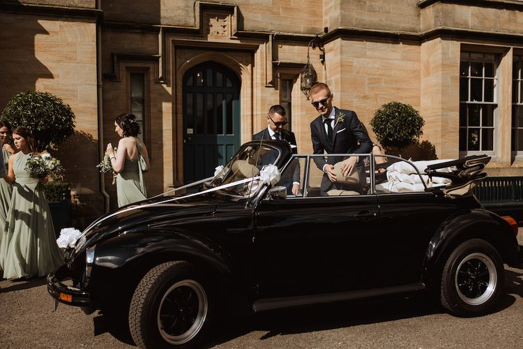 Grooms Getting into VW Beetle Wedding Car