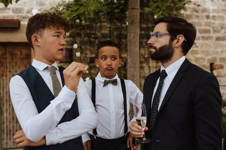 Page Boy in Braces and Bow Tie Making Face Whilst Wedding Guests are Talking