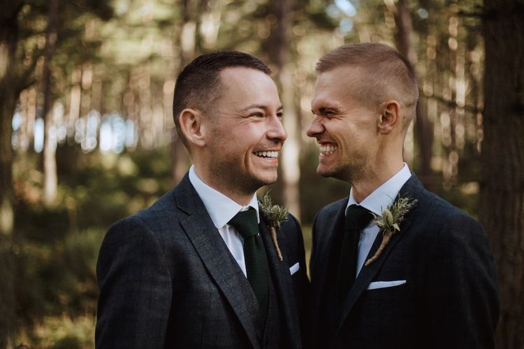 Two Grooms Smiling at Each Other in the Woods