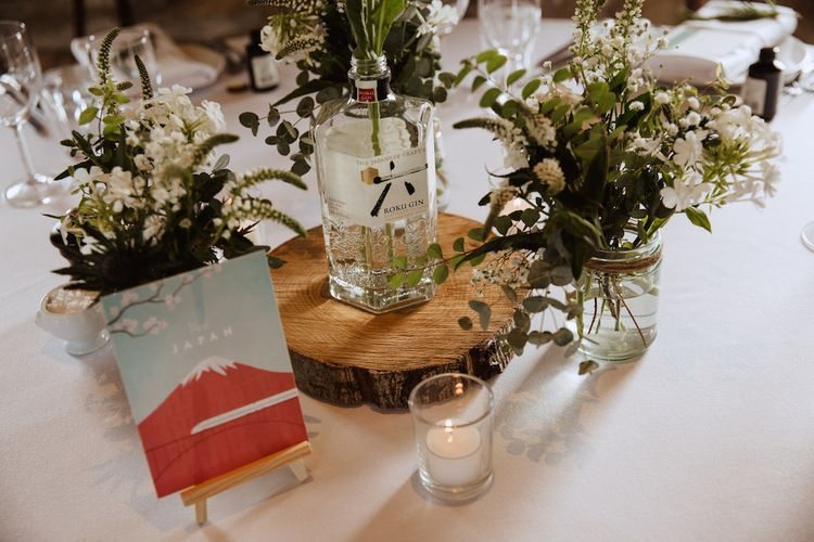 Rustic Centrepiece with Tree Slice, Gin Bottle and White Flowers in Jars