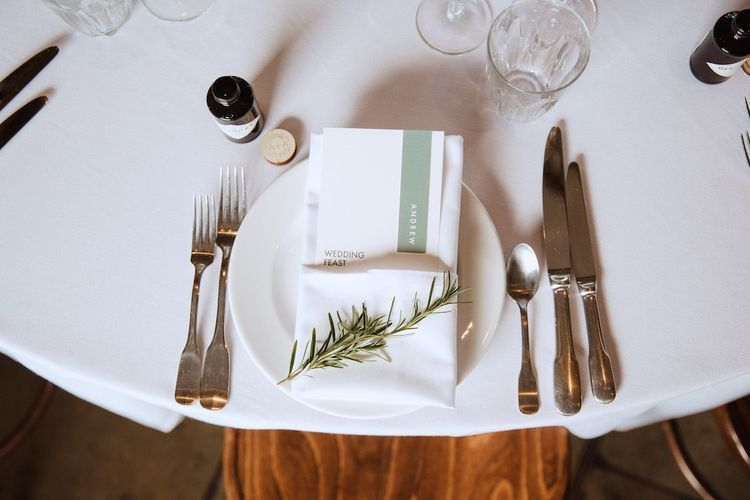 Place Setting with Menu Card Tucked into a Napkin and Decorated with a Rosemary Sprig
