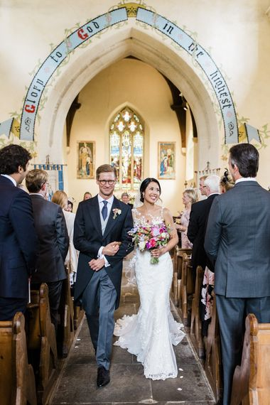 Groom in morning suits walks down the aisle with bride