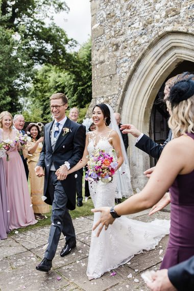 Confetti exit for bride and groom in morning suit