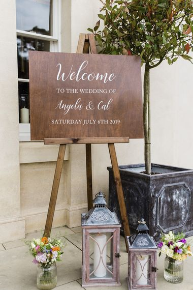 Wooden wedding signs at wedding with groomsmen in morning suits