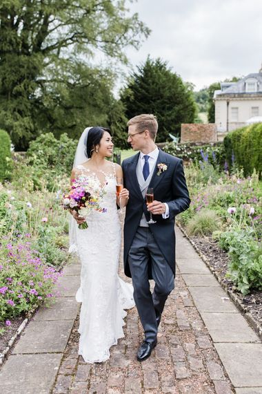 Bride with bright bouquet with groom in morning suits