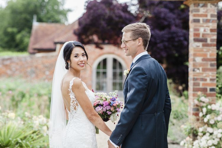 Bride in low back lace wedding dress with groom in morning suits