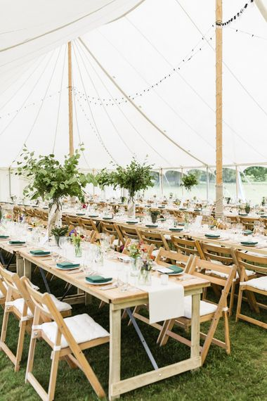 Marquee wedding table set up with floral decor and foliage bouquets