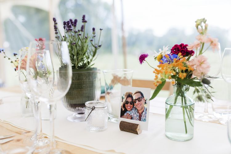 Photographic wedding table decor with small flower arrangements