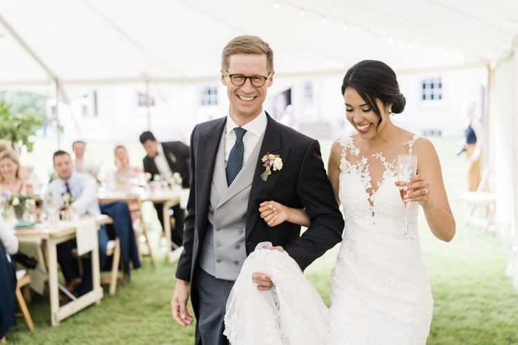 Bride and groom in morning suit enters marquee reception