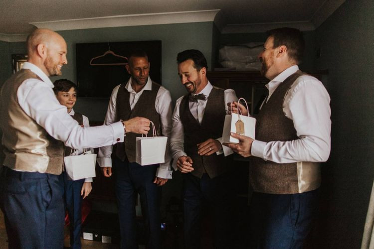 Groom and his groomsmen wearing brown waistcoats with blue suit trousers