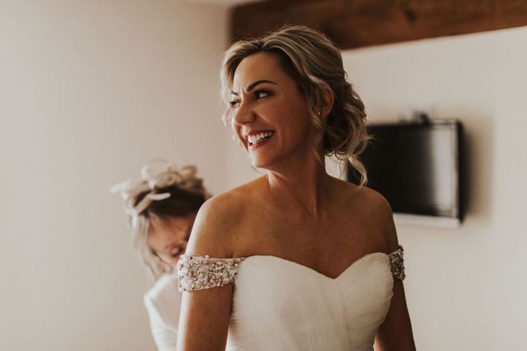 Bride wearing off  the shoulder embellished dress with sweetheart neckline and updo hairstyle
