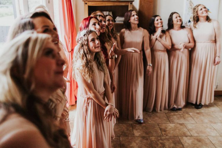 Bridesmaids wearing nude pleated dresses for outdoor summer ceremony with rose floral bouquets