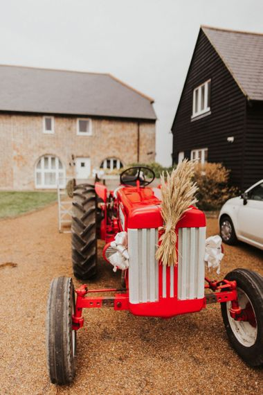 Vintage red tractor transport for outdoor summer wedding at The Ferry House Inn