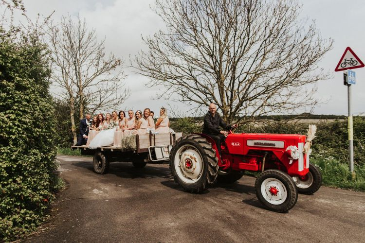Vintage red tractor transport to the ceremony for the bride and her bridesmaids wearing nude dresses
