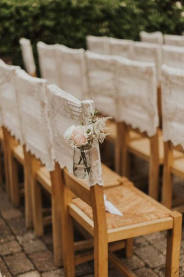 Lace chair covers and delicate pink rose decor for outdoor summer ceremony with rustic styling