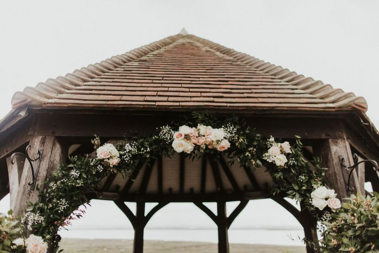 Pink rose floral archway for outdoor rustic ceremony at The Ferry House Inn