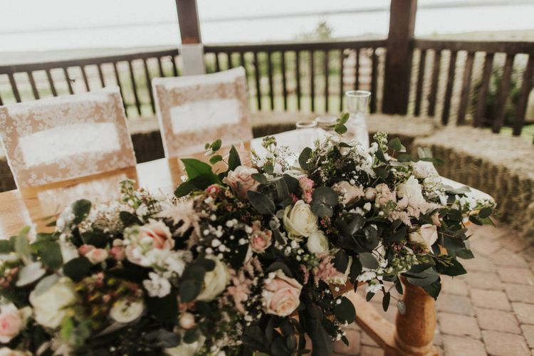 Pink rose floral decor and lace chair covers at The Ferry House Inn for an outdoor rustic ceremony
