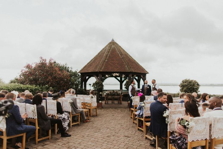 Outdoor summer ceremony at The Ferry House Inn with lace chair covers and pink rose flower decor