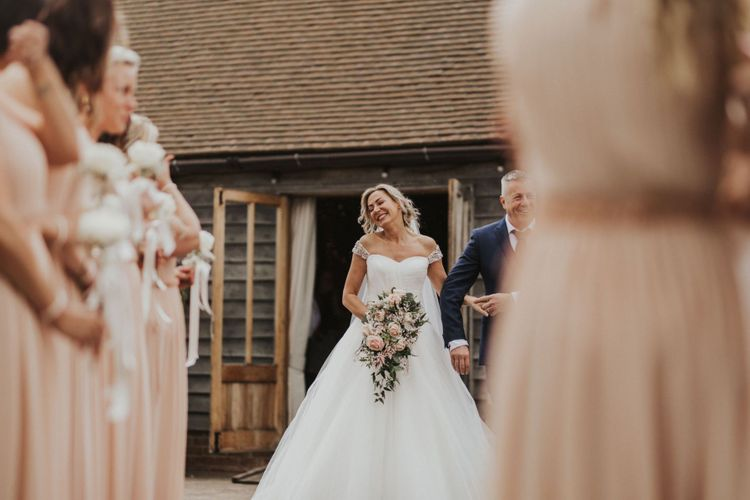 Bride wearing embellished off the shoulder sweetheart neckline dress and pink rose bouquet at The Ferry House Inn outdoor ceremony