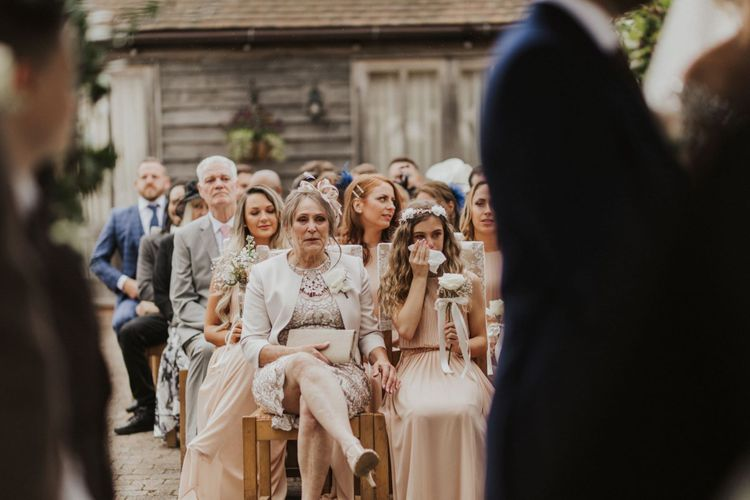 Guests at outdoor ceremony with nude bridemaid dresses and rose bouquets