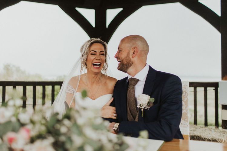 Bride and groom tie the knot at rustic ceremony with floral decor