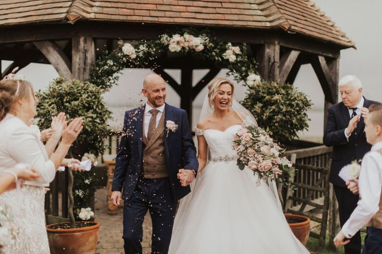 Bride and groom at outdoor ceremony with pink rose bouquet and off the shoulder bridal dress with embellished belt detail