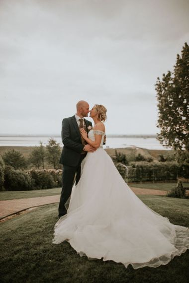 Bride wearing embellished off the shoulder dress with undo hairstyle and groom wearing navy blue suit