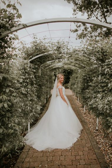 Bride wearing off the shoulder dress with embellished belt and veil at The Ferry House Inn