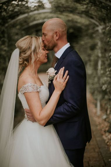 Bride and groom embrace at The Ferry House Inn with embellished off the shoulder dress and navy blue suit