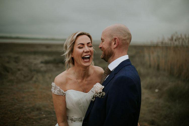 Bride and groom steal a moment at summer wedding wearing embellished of the shoulder dress