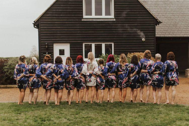 Bride and her thirteen bridesmaids wearing matching kimonos
