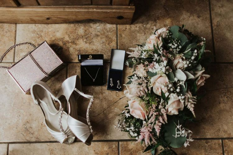 Bridal shoes and pink rose bouquet for rustic outdoor wedding in the summer