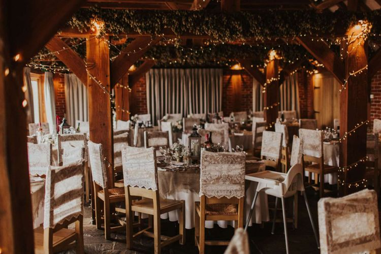 Rustic wedding reception with lace chair covers and fairy lights at The Ferry House Inn