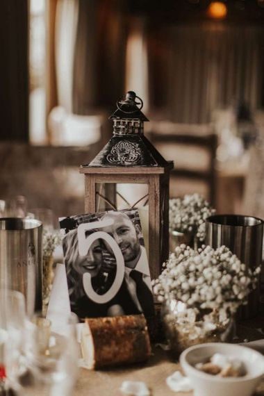 Rustic styling with photograph table numbers and lantern decor at The Ferry House Inn