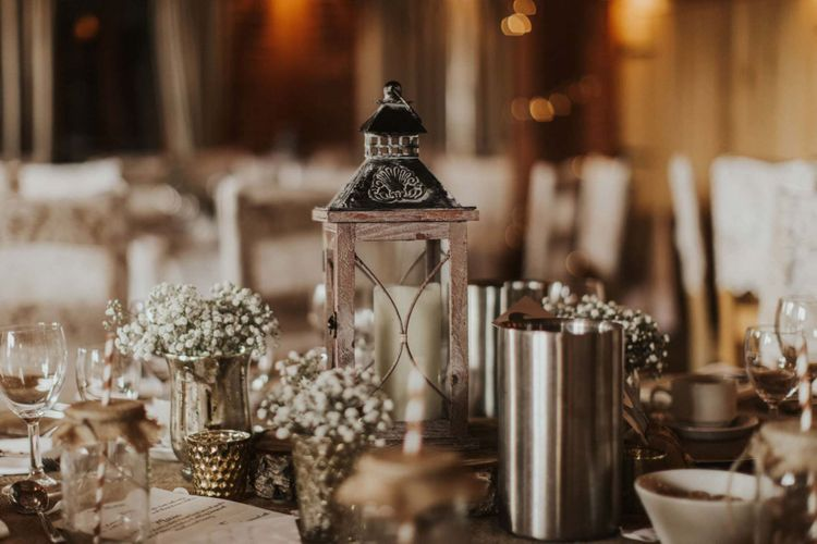 White floral decor with candle lanterns for rustic reception at The Ferry House Inn