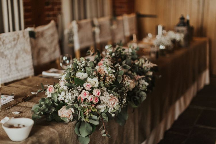 Pink rose floral decor at summer wedding with rustic styling and lace chair covers