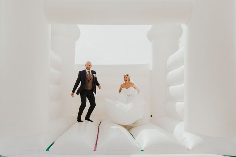 Bride and groom at outdoor celebration with white bouncy castle