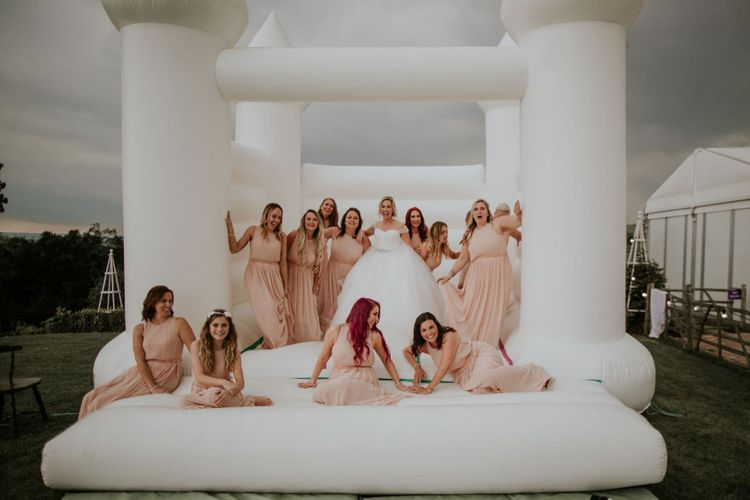 Bride and her bridesmaids wearing nude dresses enjoy white bouncy castle at The Ferry House Inn wedding