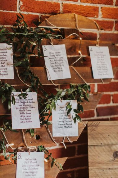 Heart shaped pallet table plan with foliage decor for rustic wedding